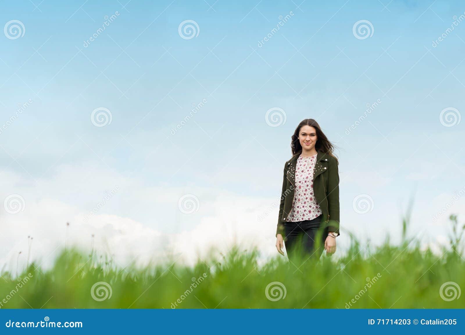 Снаружи жизнерадостной молодой женщины стоящее на зеленом луге