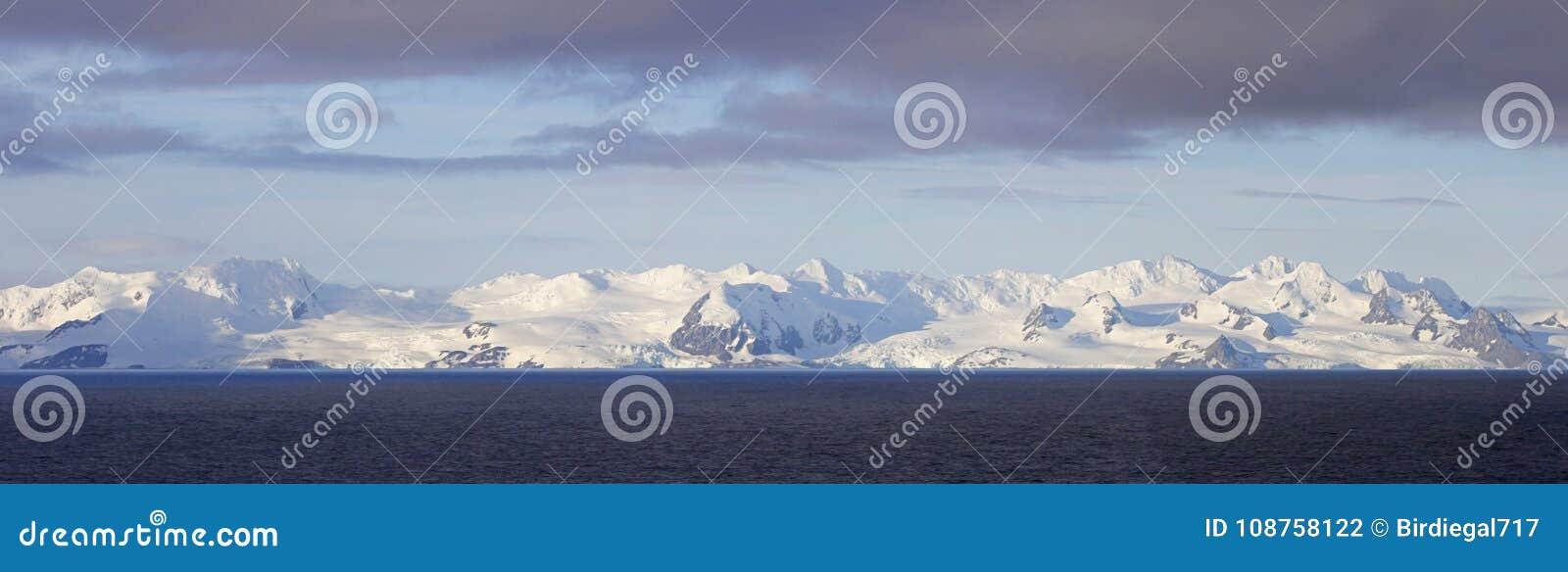 Снег Антарктики покрыл горы, стежок 4 фото панорамный Облака шторма и голубое небо