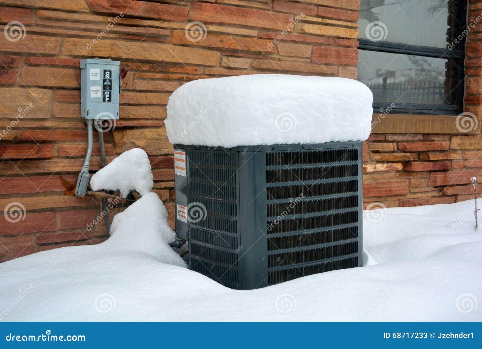Снег покрыл кондиционер воздуха на холодный зимний день