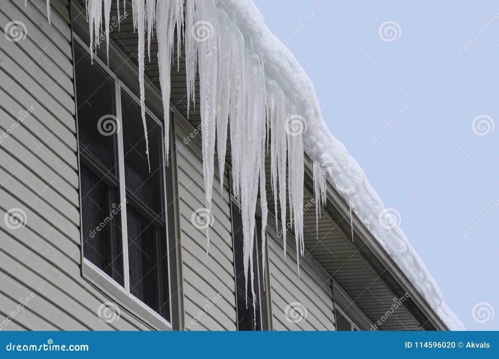 Снег предусматривал крышу при длинные сосульки вися над стрех-через