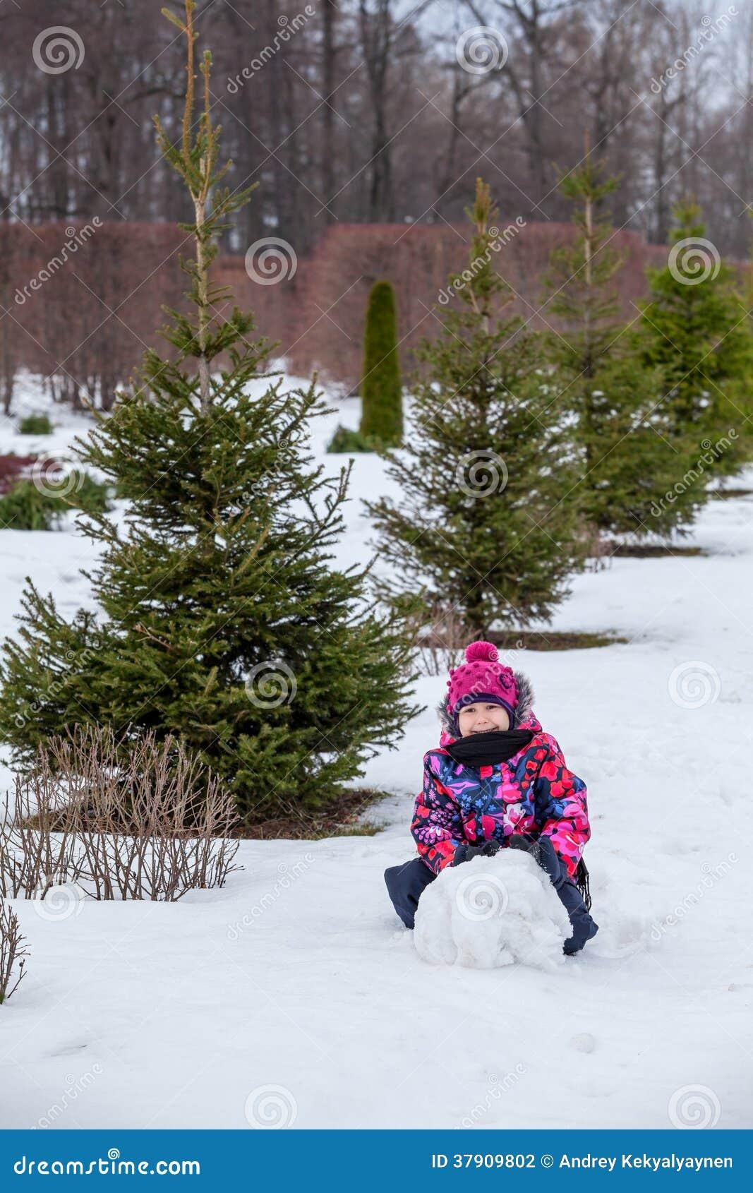 Снежный ком завальцовки маленькой девочки для снеговика на зиме