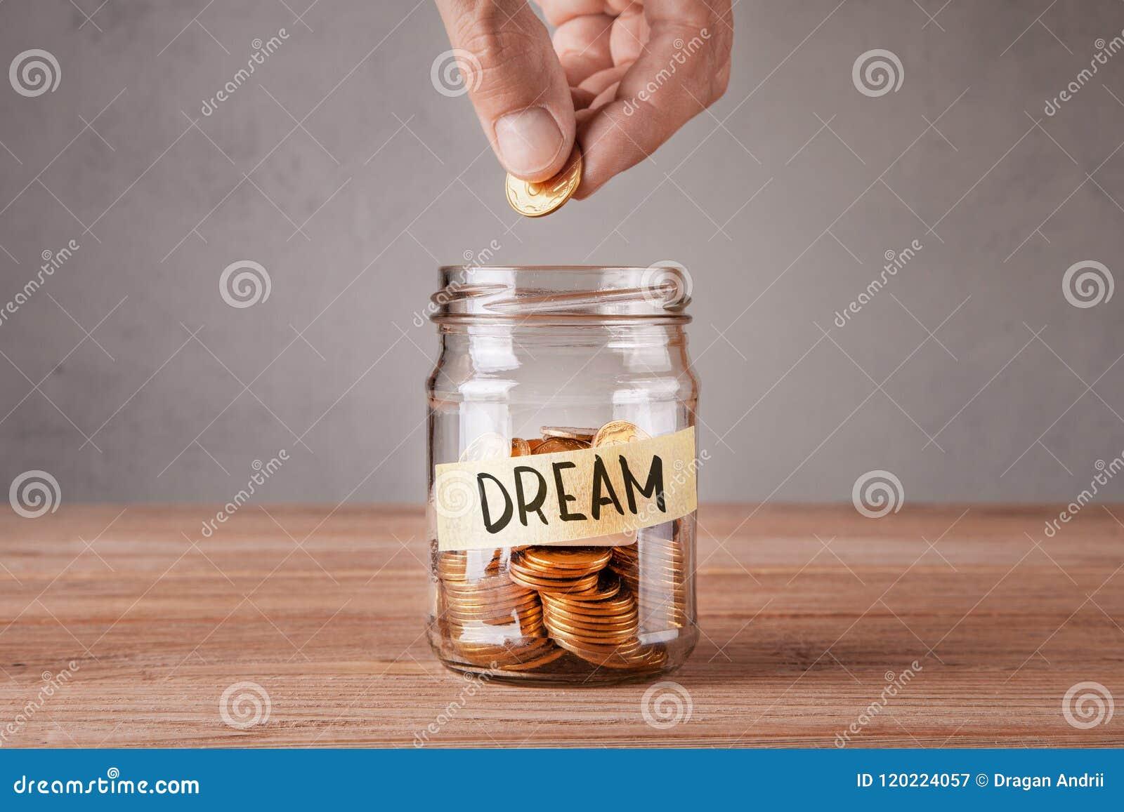 сновидение Стеклянный опарник с монетками и надпись мечтают Человек держит монетку в его руке