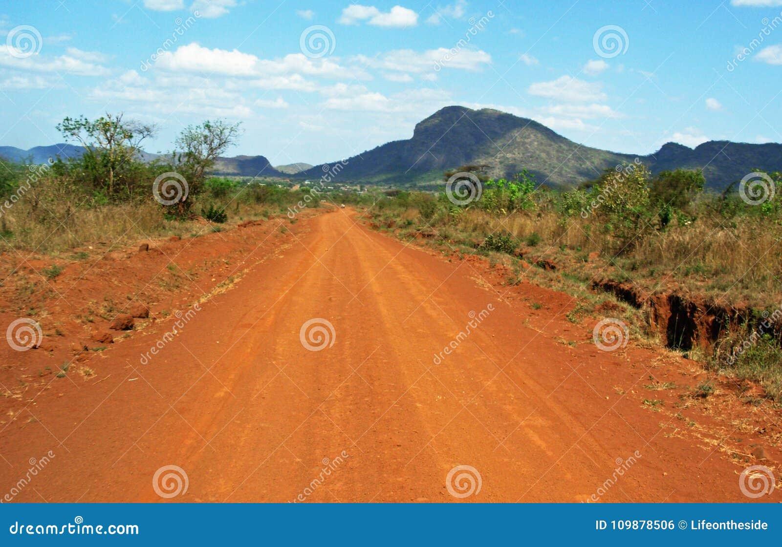 Сногсшибательный ландшафт предпосылки управляя красными пылевоздушными грязными улицами Африки