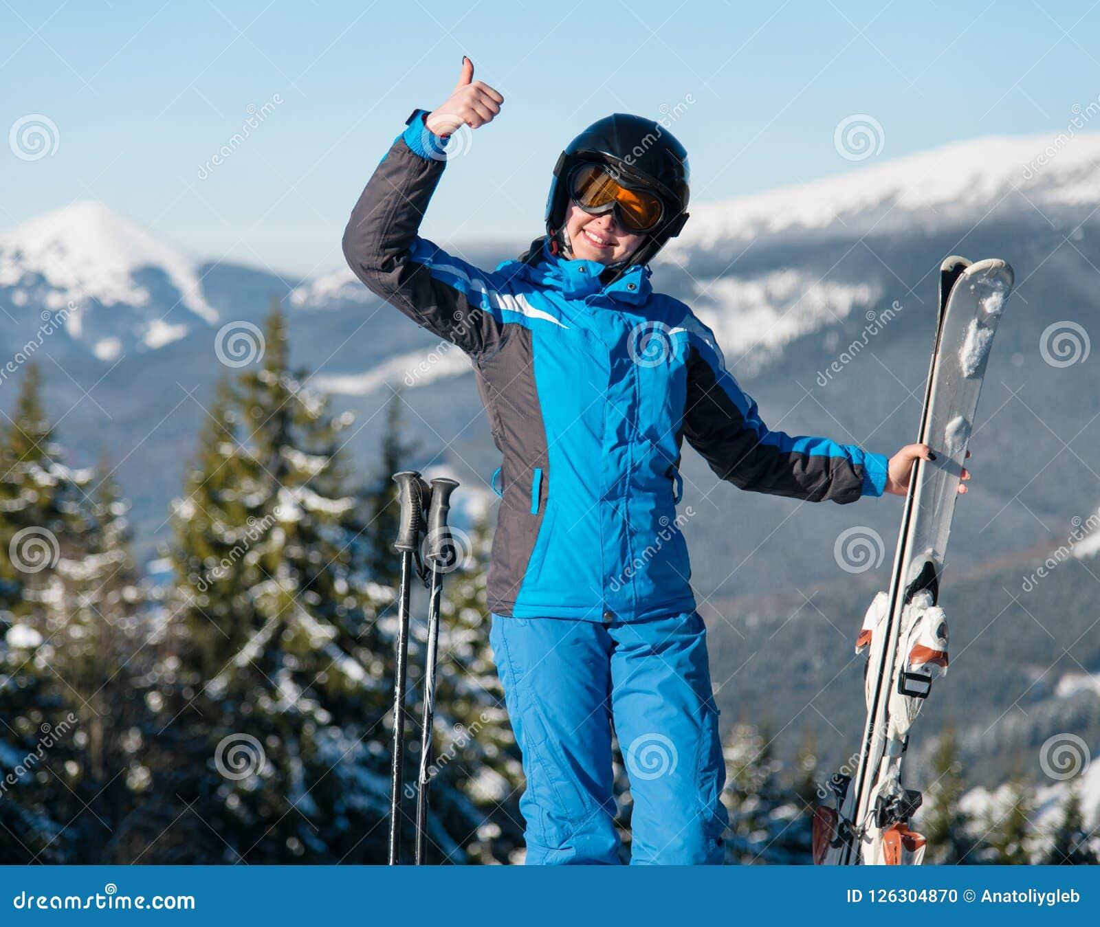 Снятый счастливый женский нося показывать шестерни катания на лыжах усмехаясь thumbs вверх по представлять в горах