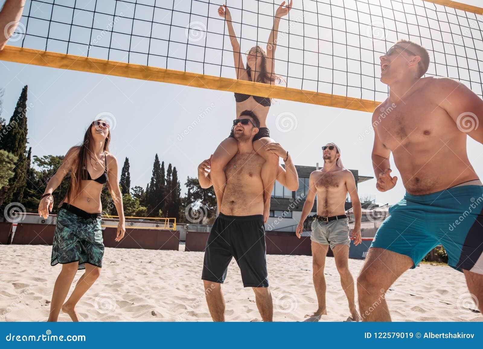 Соберите молодых кавказских друзей играя волейбол на пляже на летних каникулах