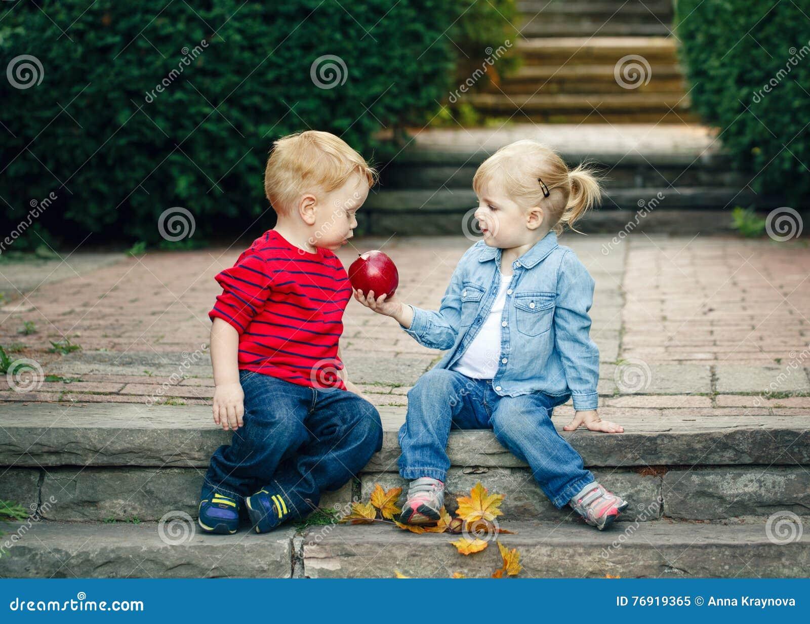Соберите портрет 2 белых кавказских милых прелестных смешных малышей детей сидя совместно делящ еду яблока