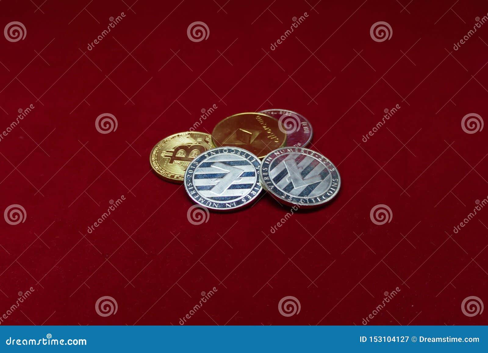 Собрание монеток cryptocurrency с litecoin во фронте и bitcoin и ethereum в задней части на красном бархате