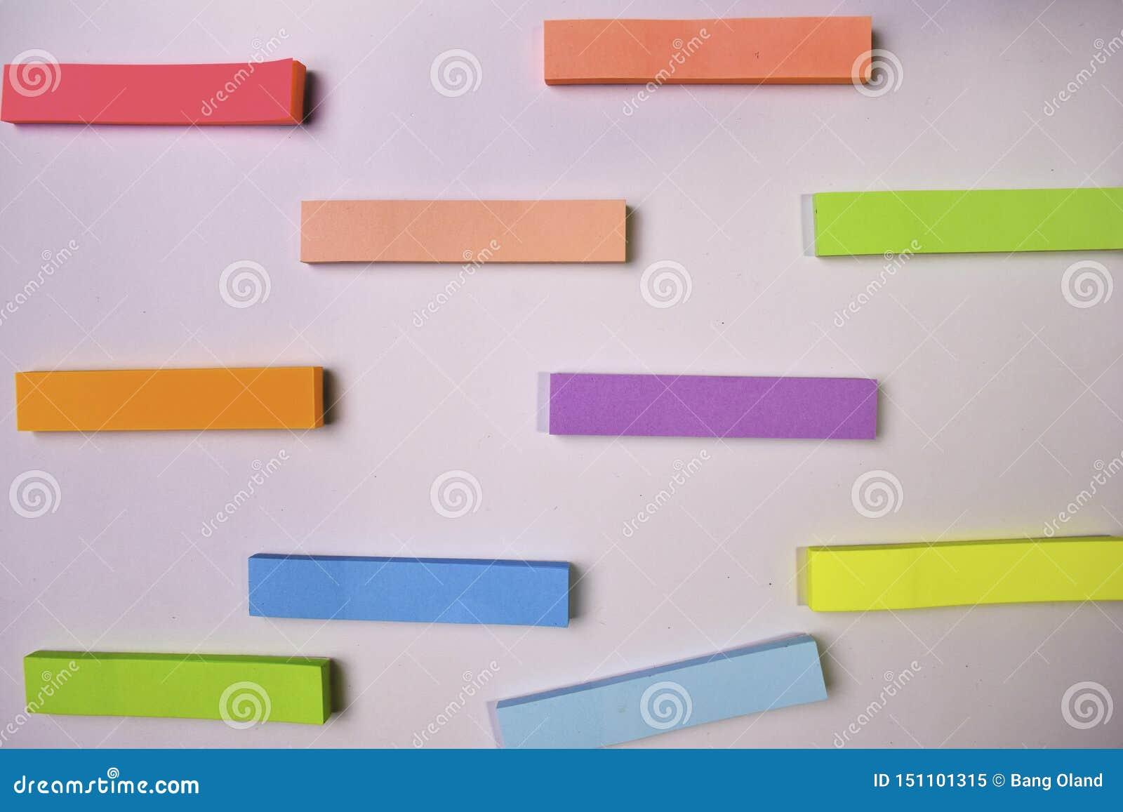 Собрание различных покрашенных листов бумаг примечания изолированных на белой предпосылке
