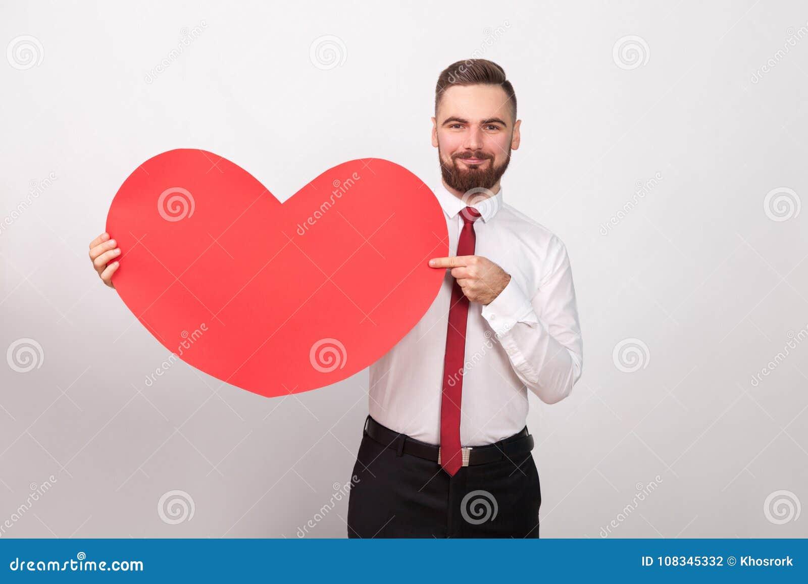 Совершенный бизнесмен усмехаясь, указывающ палец на большое красное сердце