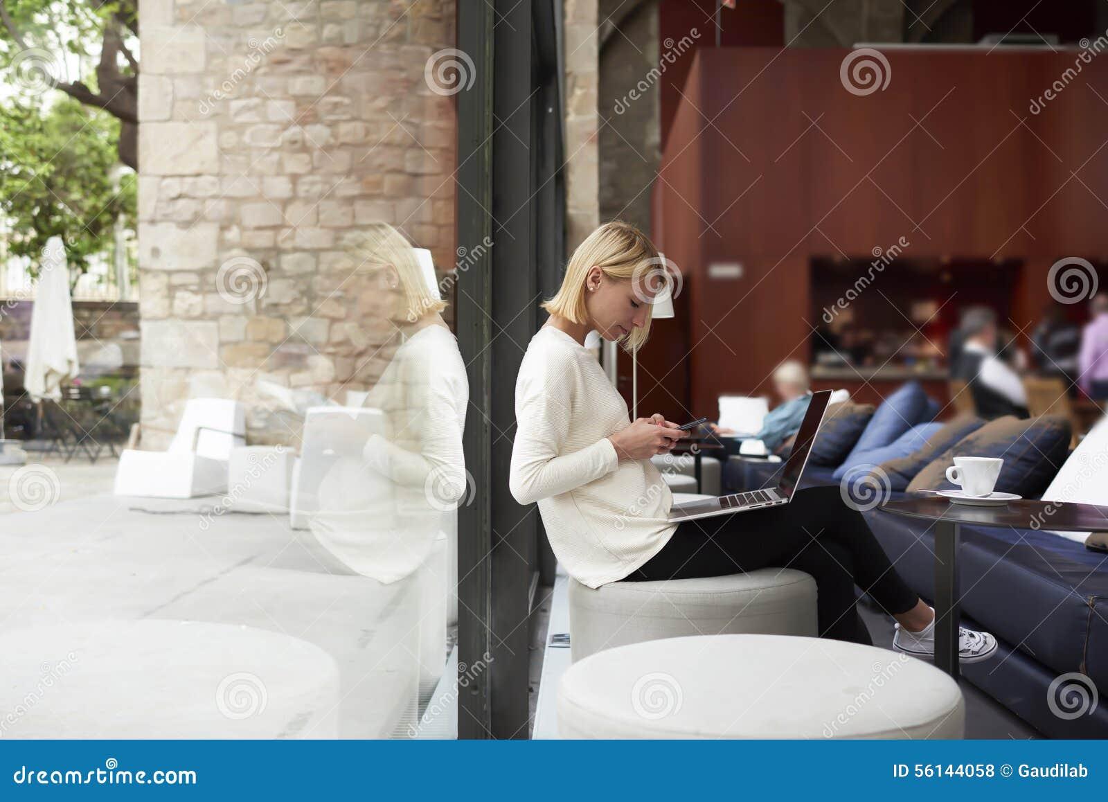 Современная бизнес-леди работая на ее сет-книге сидя на студии библиотеки или просторной квартиры с большими окнами