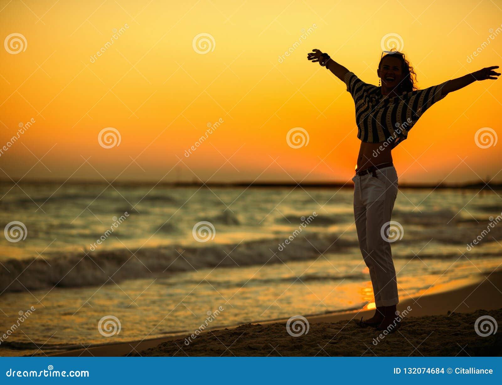 Современная женщина на пляже на ликовании захода солнца