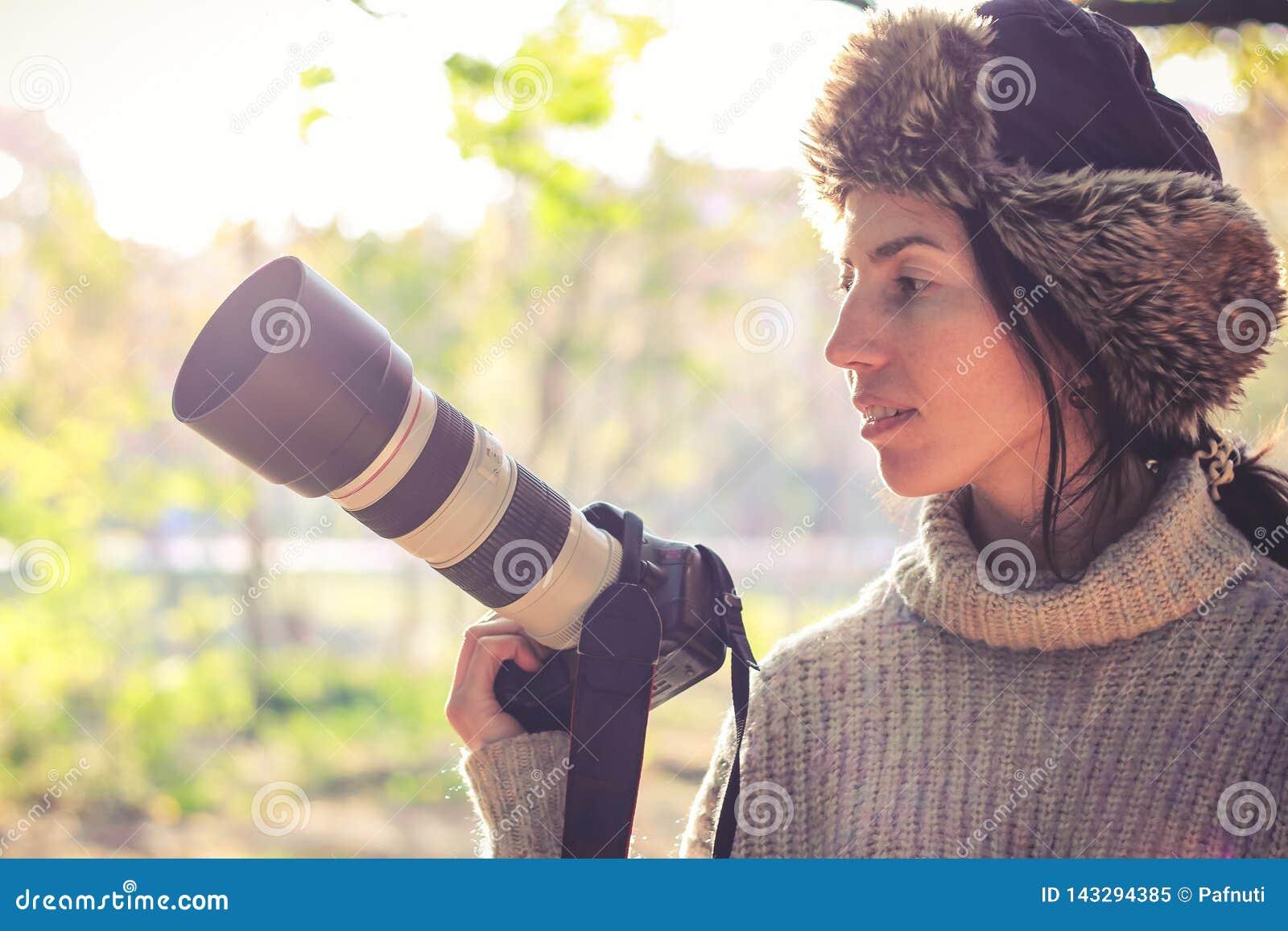 Современная камера с большим объективом в руке молодой девушки фотографа и готовый для того чтобы принять фото