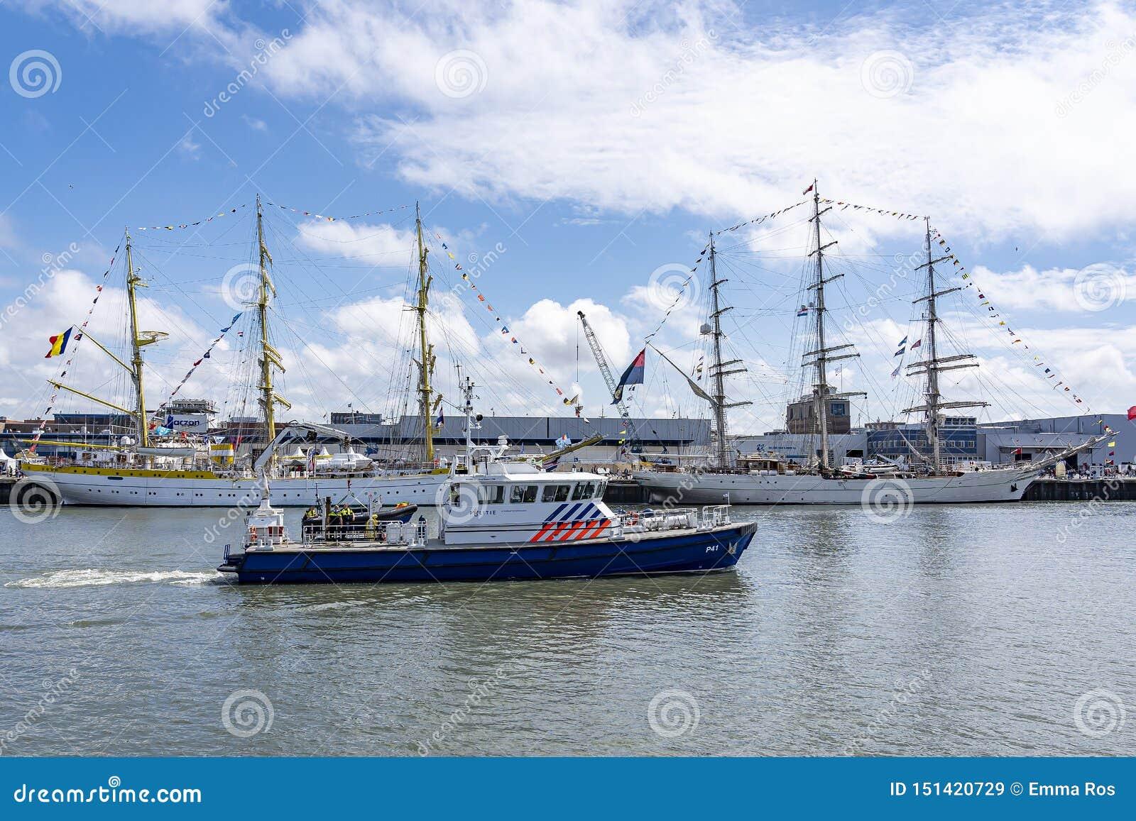 Современная шлюпка полиции проходит Tallships Mircea и Shabab Оман II, в гавани Scheveningen во время ветрила на Scheveninge