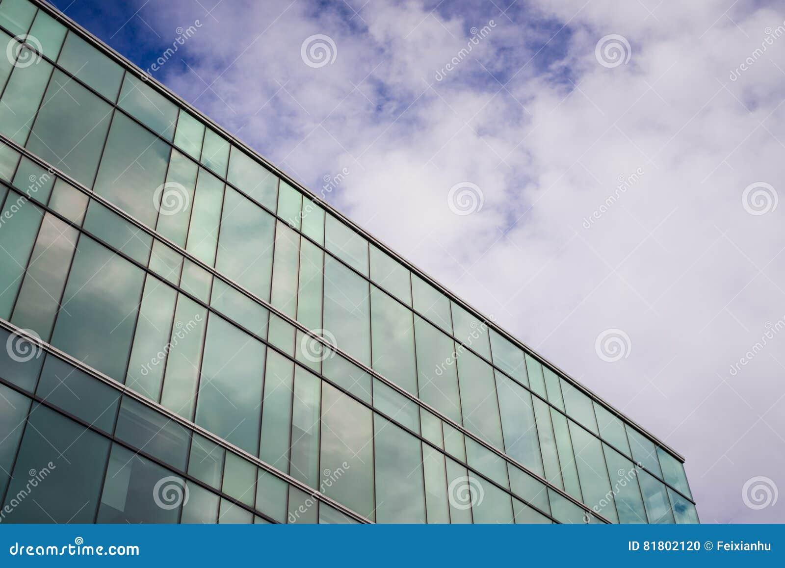 Современное офисное здание стиля с голубым небом и облаком на заднем плане