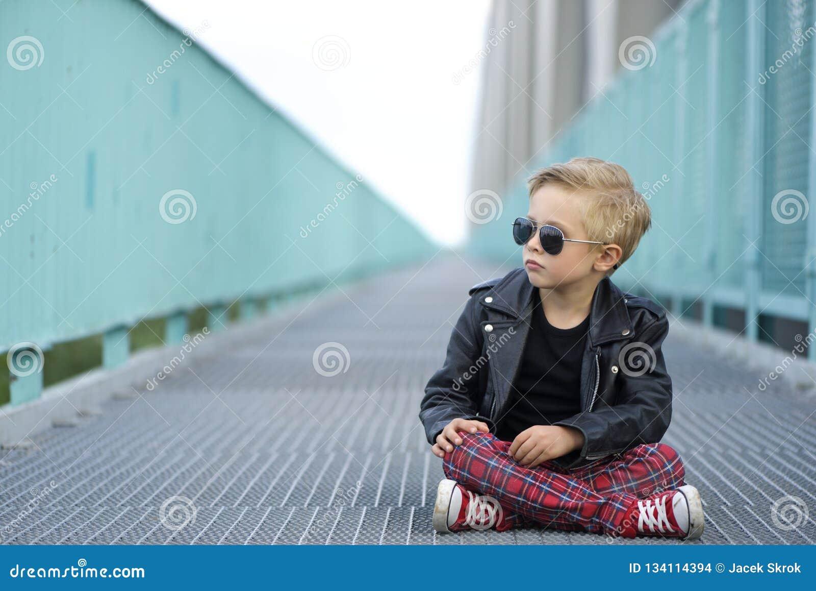 Современно одетый мальчик, представляет как модель
