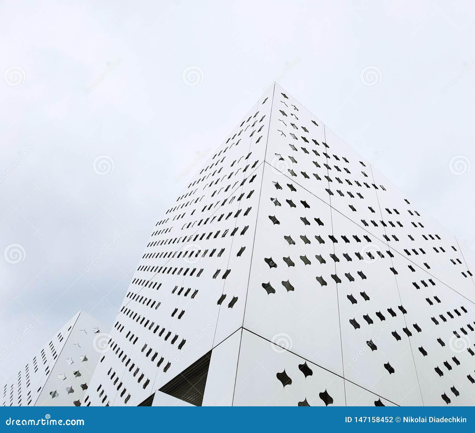 Современные здания необыкновенных форм от белого пефорированного металла
