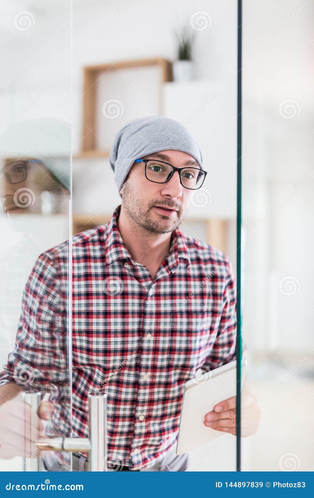 Современный бизнесмен держа цифровой планшет пока приходящ вне от его