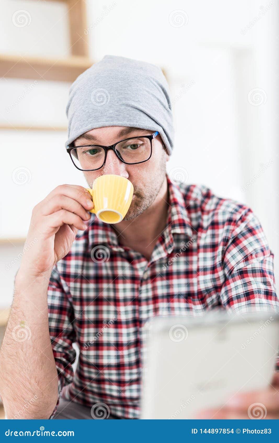 Современный дизайнер наслаждаясь его кофе утра и держа цифровой планш