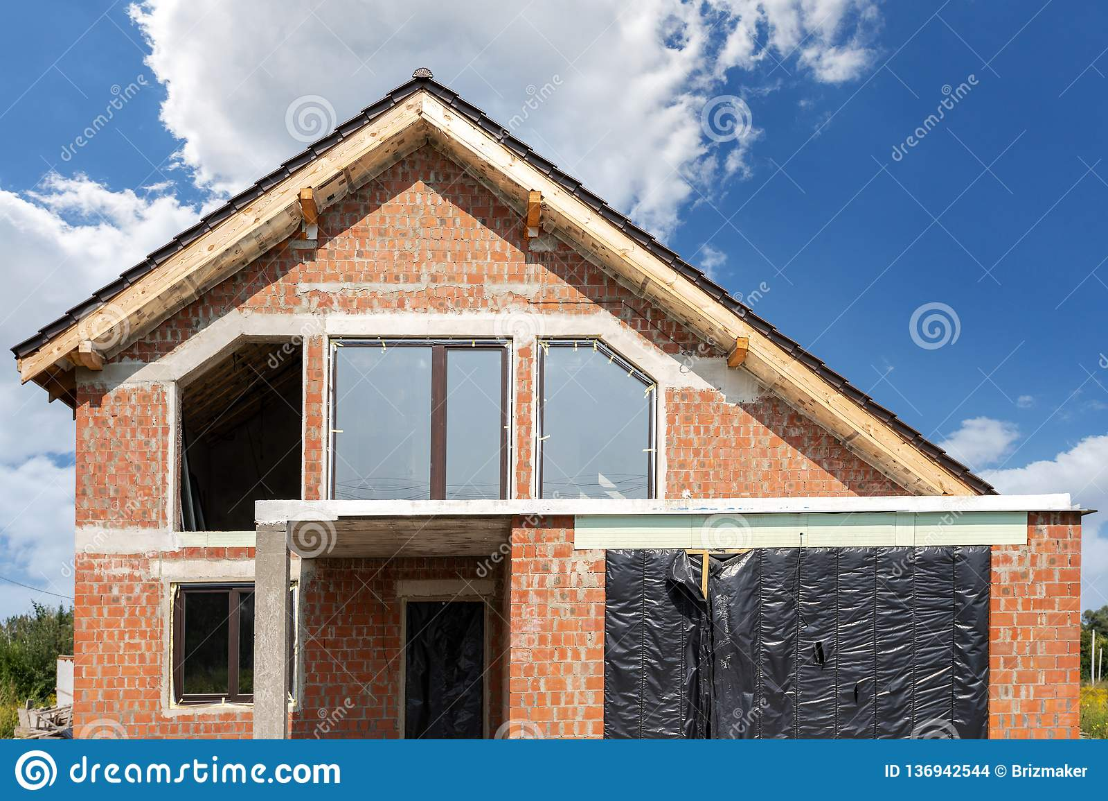 Современный дом кирпича под конструкцией против голубого неба