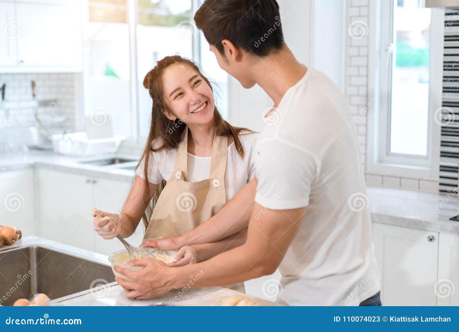 Соедините варить хлебопекарню в комнате кухни, молодом азиатском человеке и женщине совместно