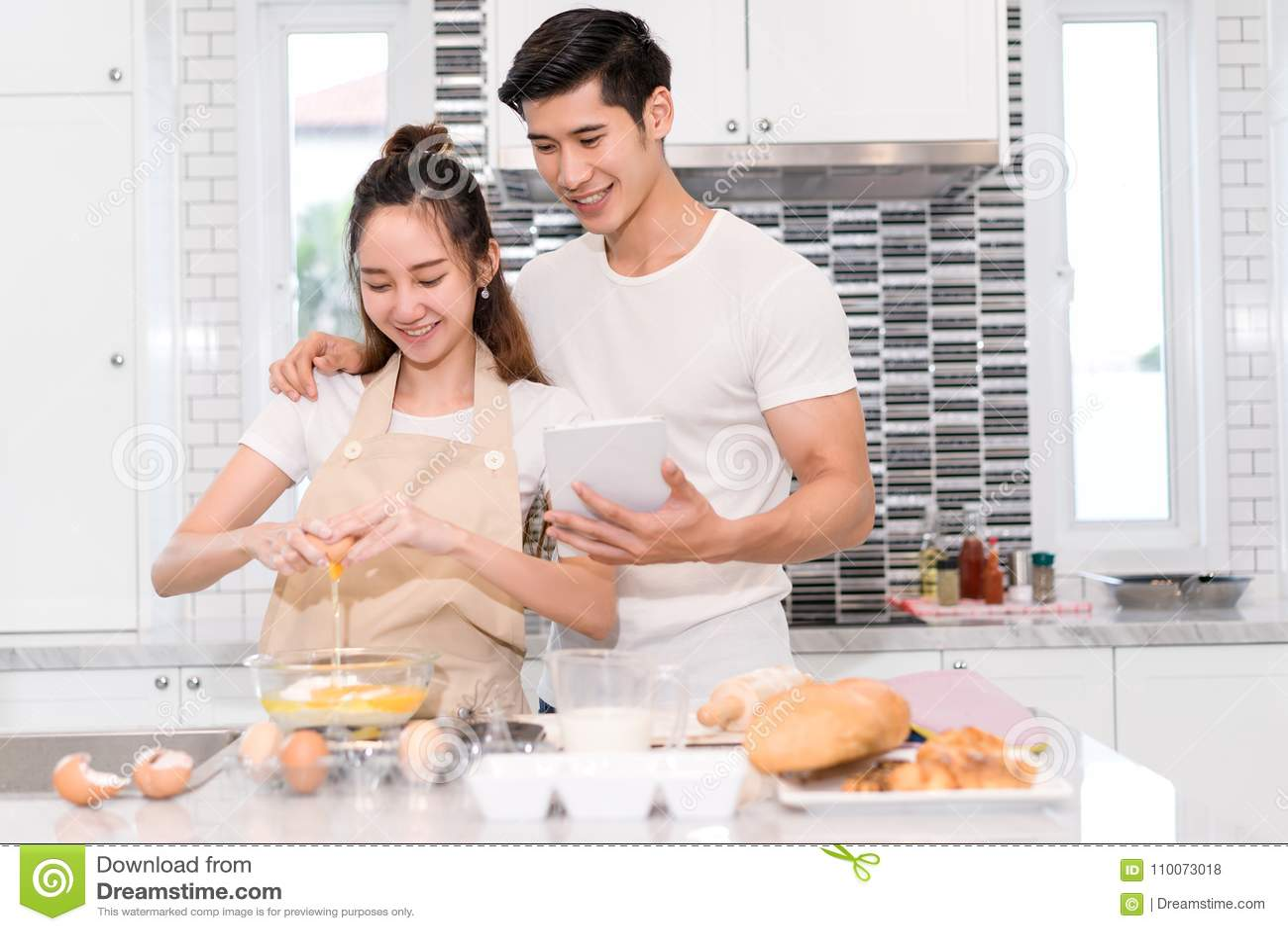 Соедините делать хлебопекарню, торт в комнате кухни, молодой азиатский человека и женщину