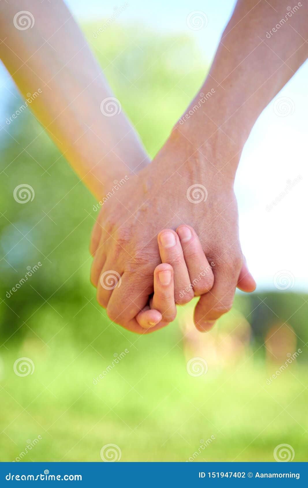 Соедините удержание рук и идти в солнечную погоду лета