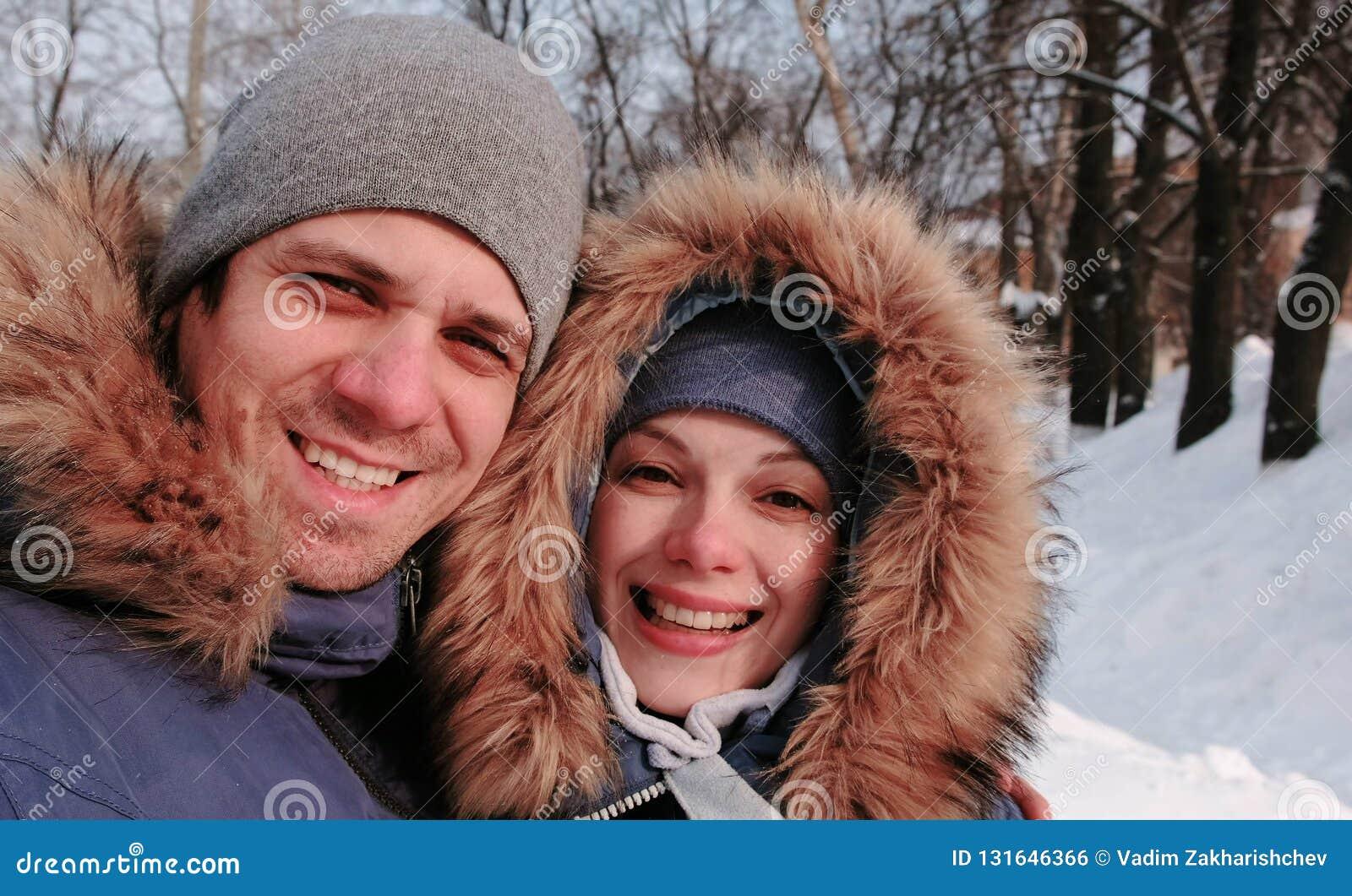 Соедините человека и женщины говоря на видео- соединении и идя в парк города зимы в снежном дне с падая снегом