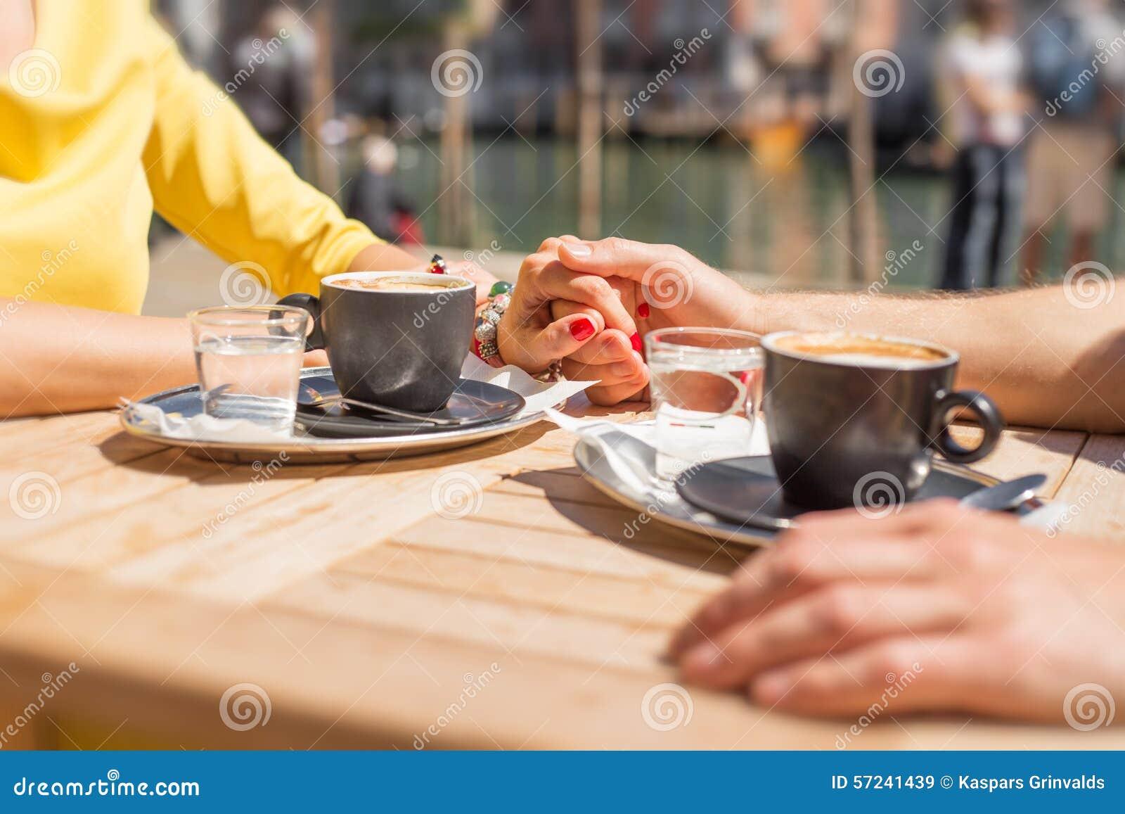 Соедините держать руки и выпивать кофе в кафе outdoors