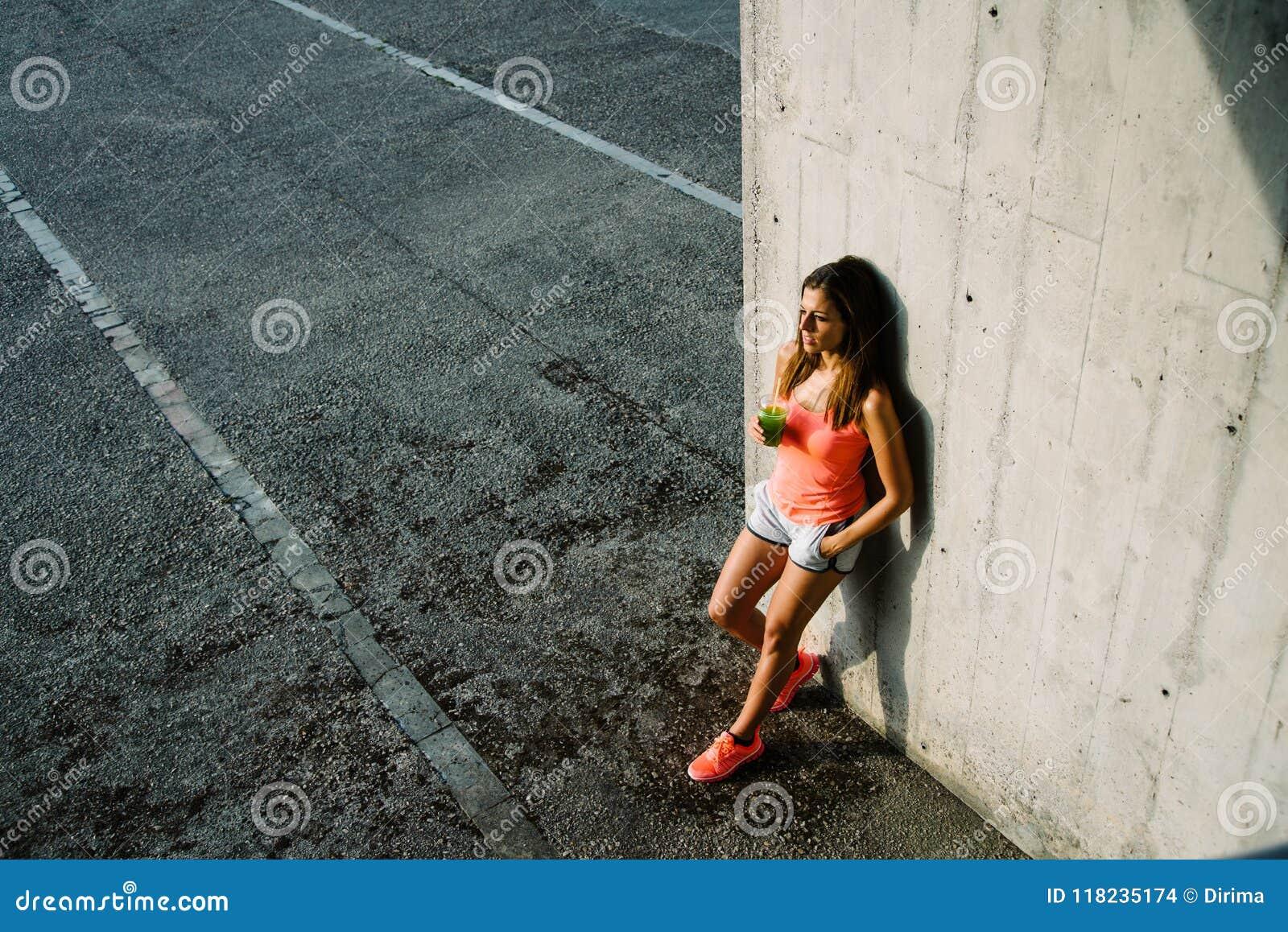 Сок и отдыхать вытрезвителя расслабленной sporty молодой женщины выпивая