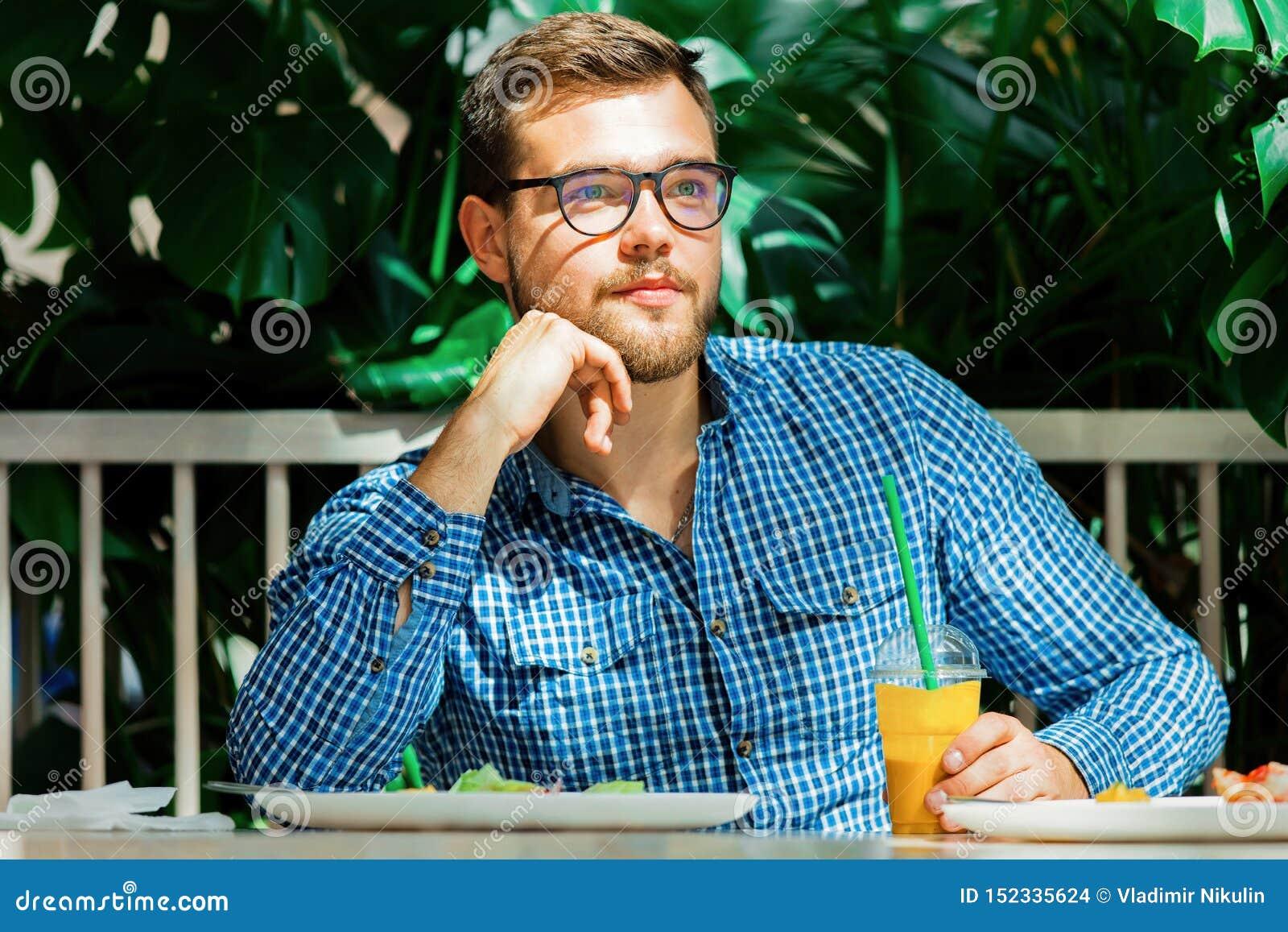 Сок молодого человека выпивая в кафе