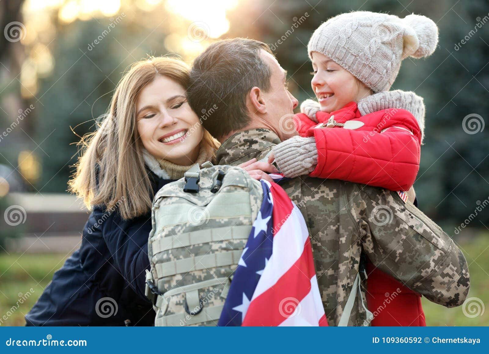 Солдат США обнимая его семью