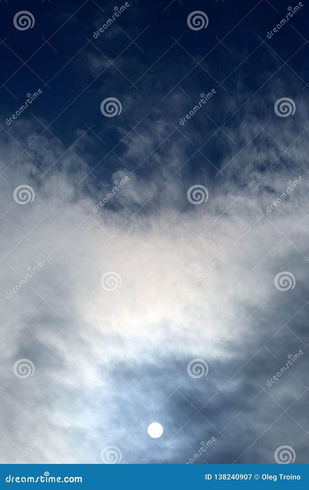 Солнечный диск в полдень через облака