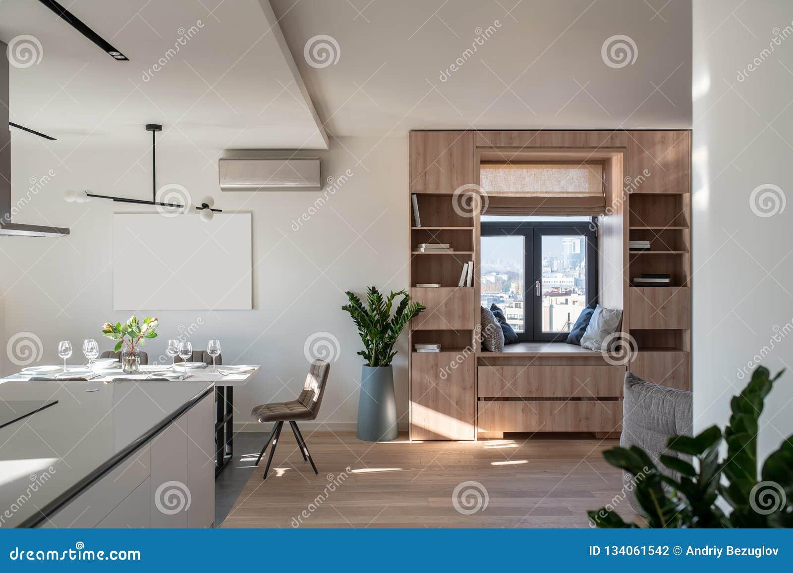 Солнечный современный интерьер с белыми стенами и зоной кухни