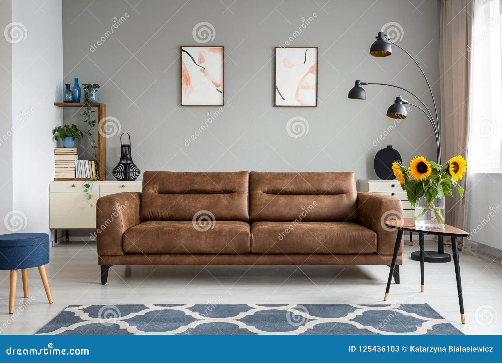 Солнцецветы на деревянном столе рядом с кожаной софой в интерьере живущей комнаты с плакатами Реальное фото
