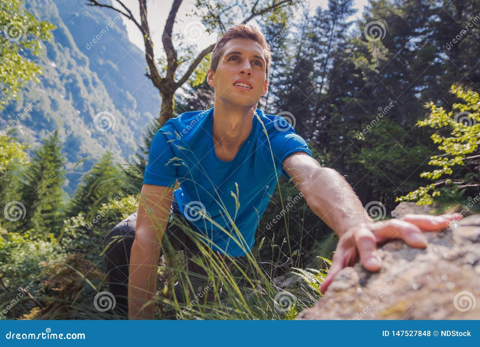 Сольный человек взбираясь утес в лесе