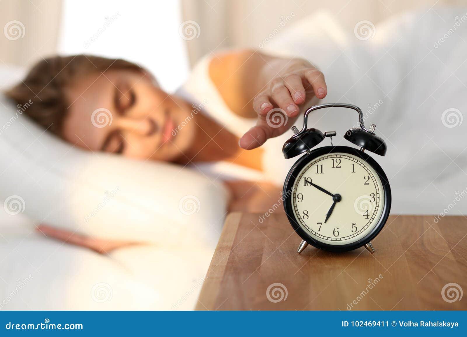 Сонная молодая женщина протягивая руку к звеня повороту сигнала тревоги охотно готовому оно  Предыдущее бодрствование вверх, не п