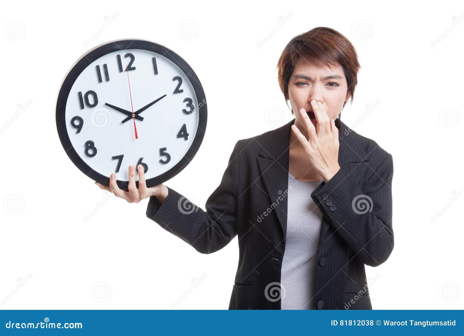 Сонная молодая азиатская бизнес-леди с часами в утре