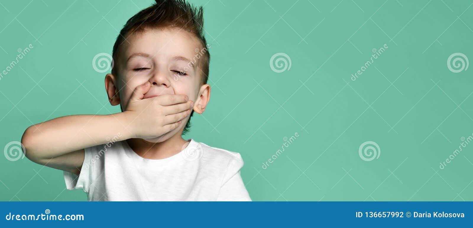 Сонный мальчик зевая и смотря изолированную камеру