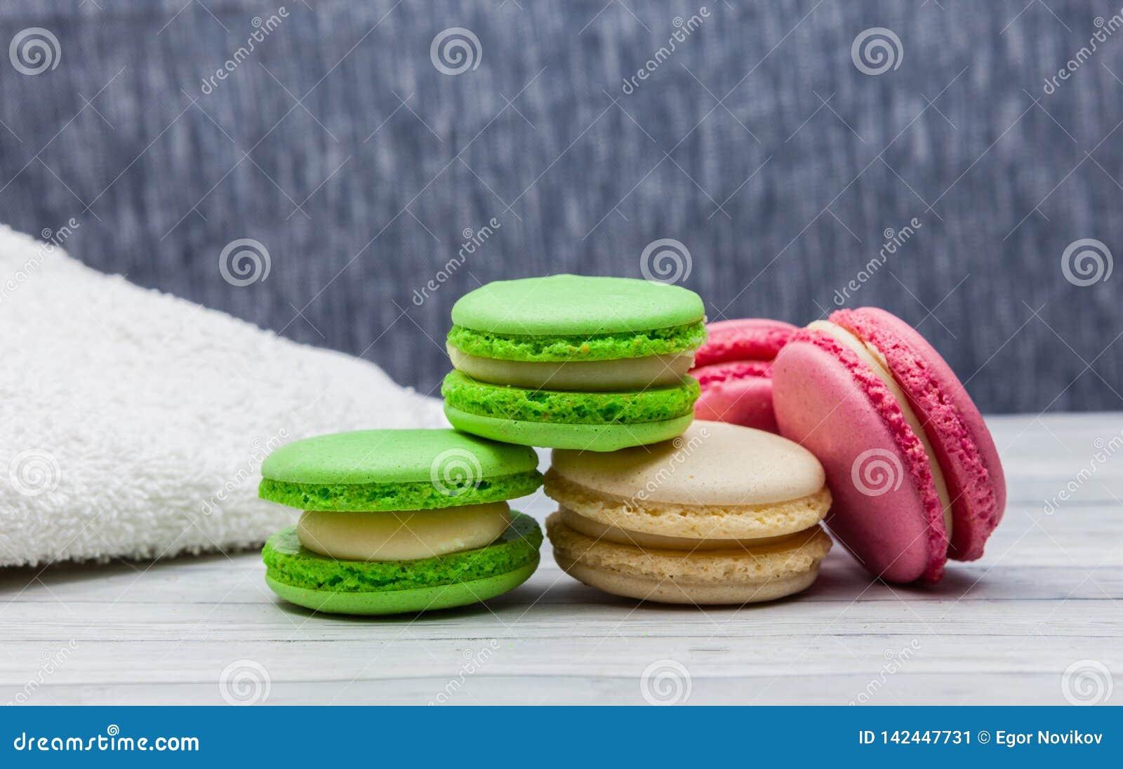 Сортированные красочные macaroons на деревянном столе и голубой предпосыл