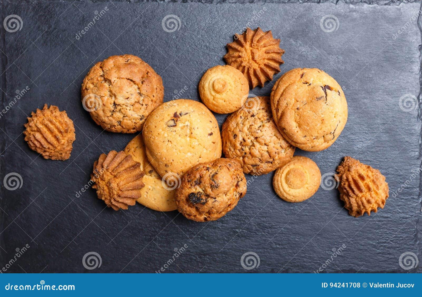 Сортированные печенья с обломоком шоколада, изюминкой овсяной каши на каменной предпосылке шифера на деревянном конце предпосылки
