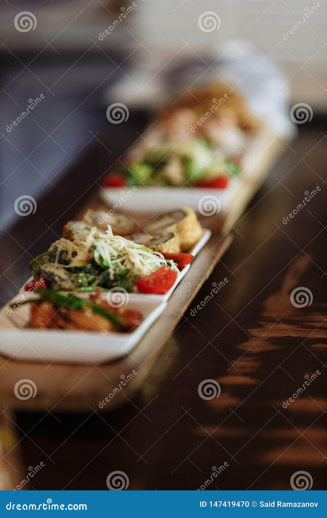 Сортированные японские блюда в белых квадратных плитах на деревянных стойках на предпосылке таблицы