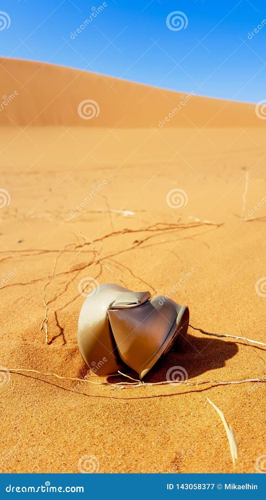 Сор в пустыне, ржавая консервная банка на песке в пустыне