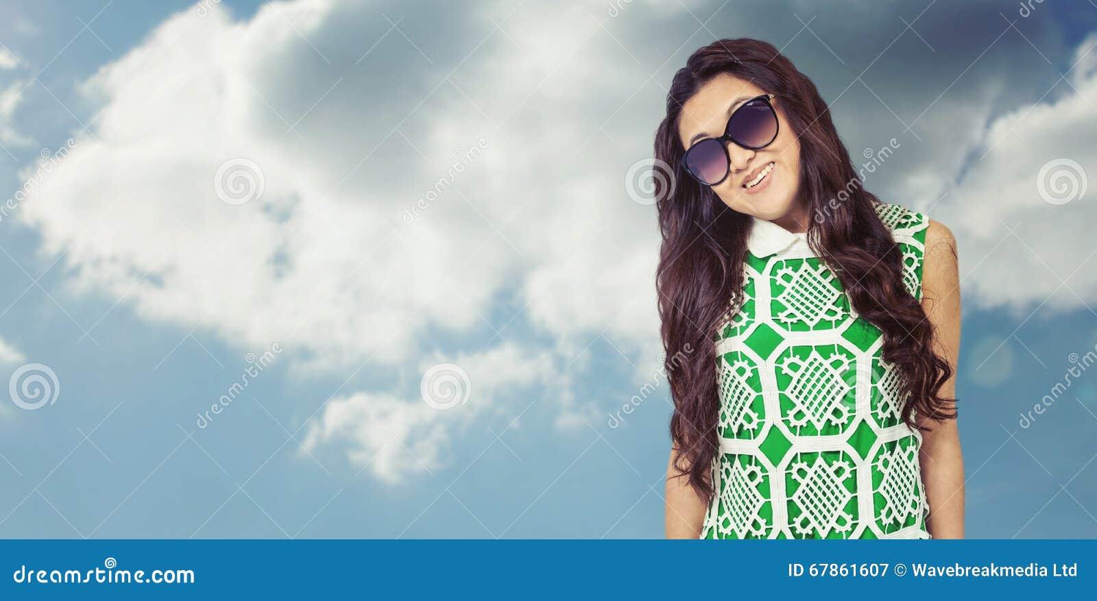 Составное изображение азиатской женщины при солнечные очки представляя для камеры