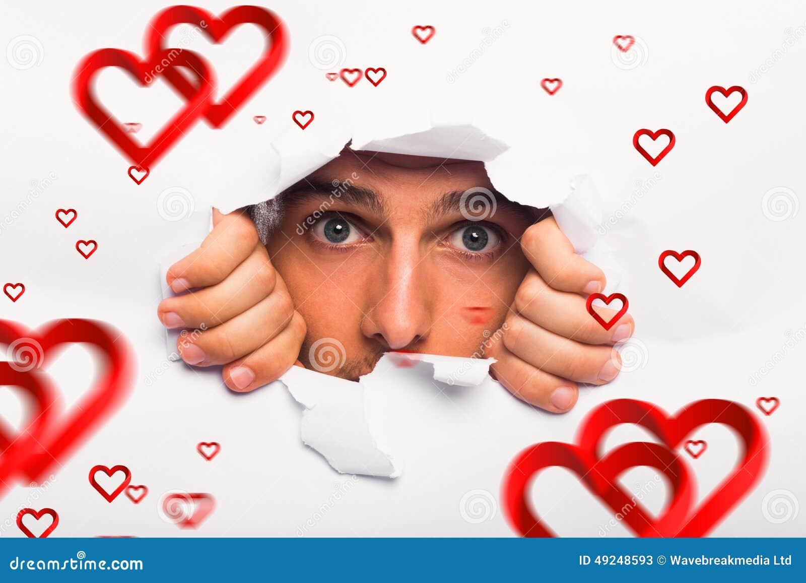 Составное изображение молодого человека смотря через бумажный сулой