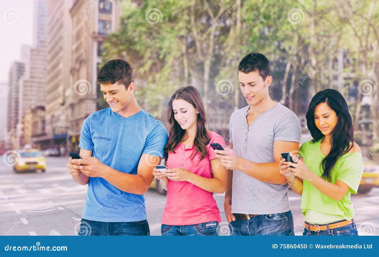 Составное изображение 4 друзей стоя к стороне немножко посылая отправляет СМС
