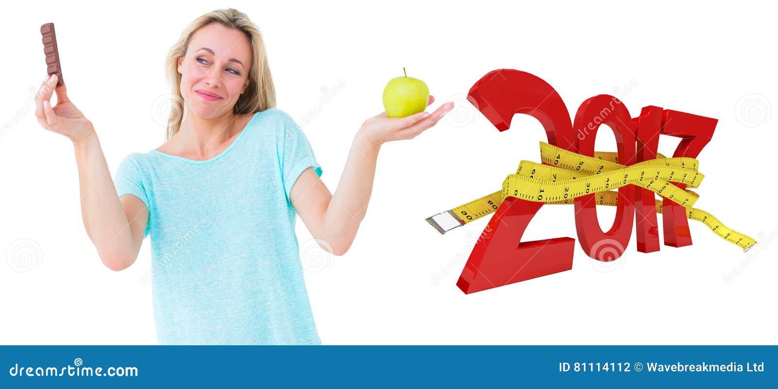составное изображение 3D усмехаясь белокурого держа бара шоколада и яблока