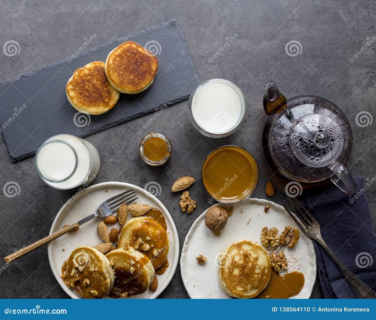 Состав завтрака с блинчиками, молоком и чаем на черной предпосылке