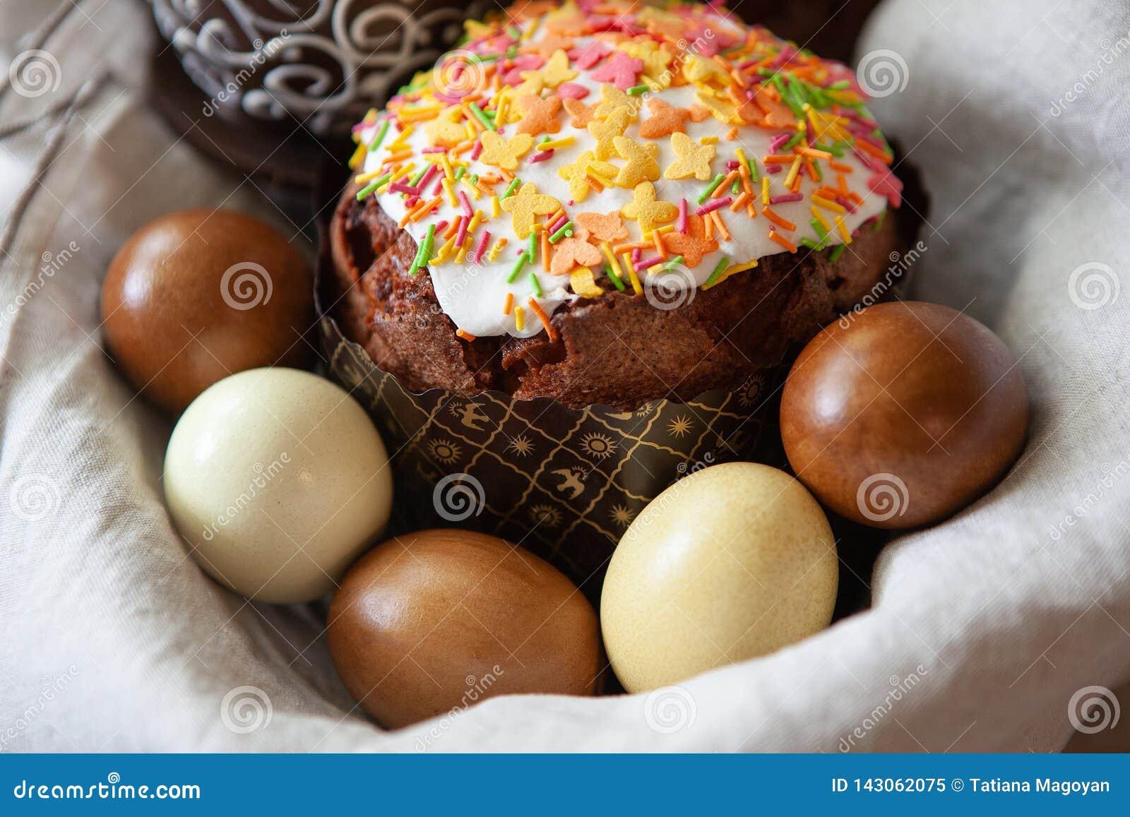 Состав пасхи с аппетитным, красиво украшенным тортом пасхи, покрасил яйца в корзине на ткани белья, конце-вверх, взгляде со сторо