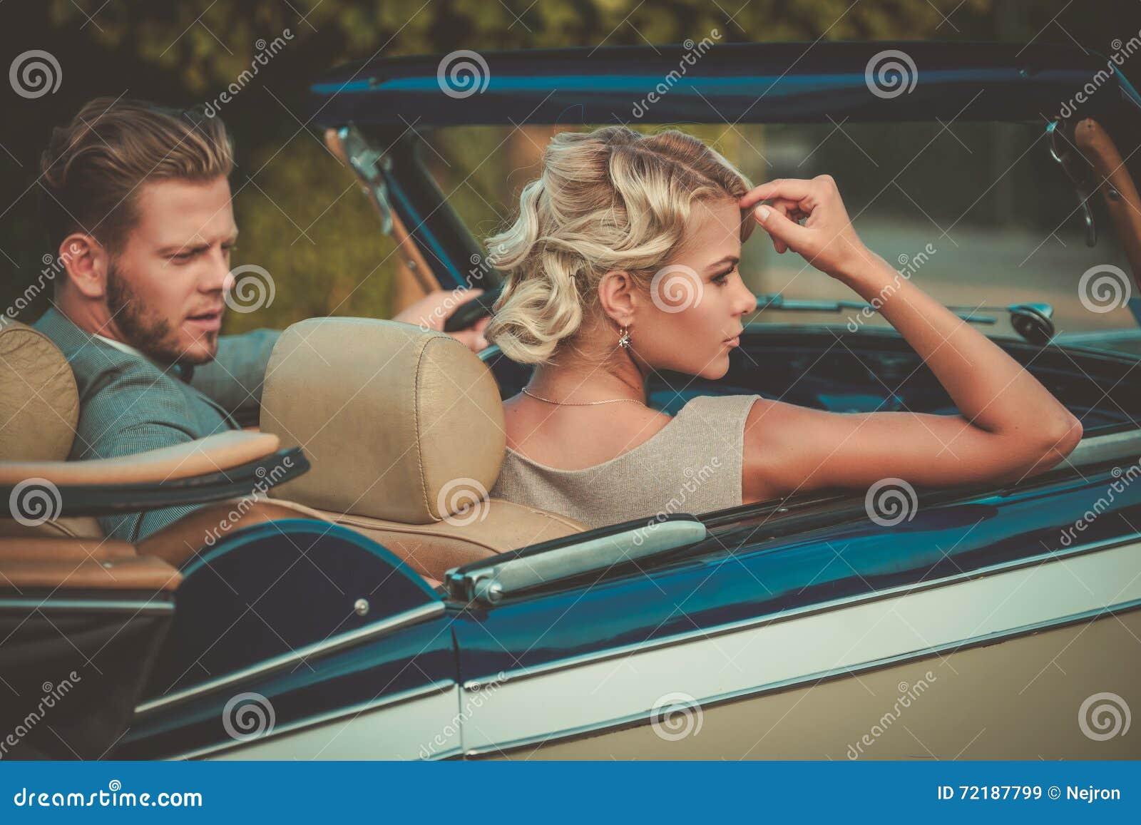 Состоятельные молодые пары в классическом автомобиле с откидным верхом