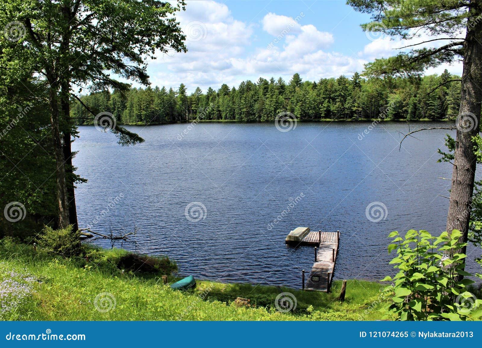 Состыкуйте на пруде Леонарда расположенном в Childwold, Нью-Йорке, Соединенных Штатах
